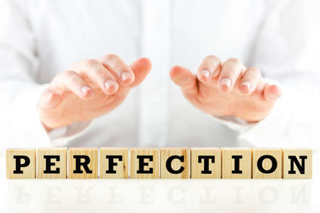wholeness: Man holding his hands protectively over the word Perfection on a row of wooden cubes in a conceptual image, closeup of the cubes and hands. Stock Photo