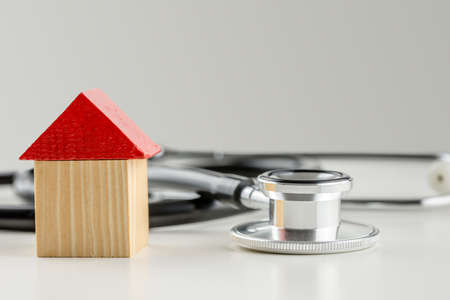 Wooden toy house next to a stethoscope. Conceptual image of solution to the real estate market crisis. photo