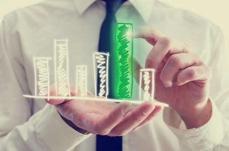 그는 감동과 가상 컴퓨터 인터페이스처럼 그의 손가락으로 활성화되는 단일 높은 녹색 막대와 그의 손에 손으로 그린 막대 그래프를 들고 사업가