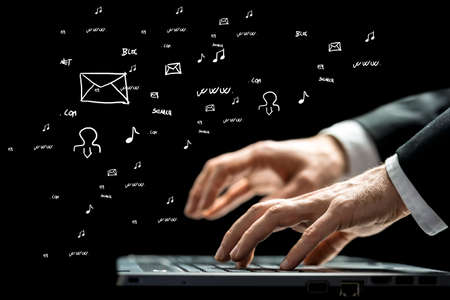 randomly: Businessman typing on a computer keyboard against a blackboard with hand-drawn business and computer icons scattered randomly, low angle view. Stock Photo