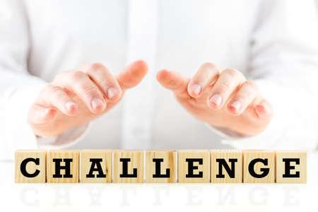 Conceptueel beeld met het woord Challenge op houten blokken of blokjes beschermd door de handen van een man die hen beschutten van boven. Stockfoto - 27307128