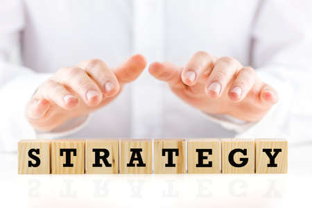 gimmick: Man holding his hands protectively over the word Strategy on a row of wooden cubes in a conceptual image, closeup of the cubes and hands  Stock Photo