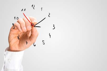 puntualidad: Hombre a�adiendo una segunda mano para un reloj a mano en una interfaz virtual con una pluma roja marcador en un concepto de plazos, la gesti�n del tiempo y la puntualidad