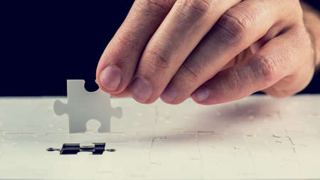 Close up of the hand of a man placing the last piece in place in a jigsaw puzzle conceptual of problem solving, finding a solution and meeting a challenge