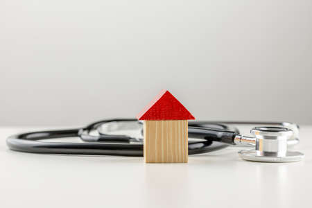 Conceptual image of a medical stethoscope lying on a white surface with a small wooden model of a house with a bright red roof with copyspace on grey above  photo