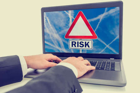 Hands of a businessman in a suit sitting typing on a laptop with a sign displayed on the screen saying - Risk - on a triangular traffic sign against a blue sky in a conceptual image. photo