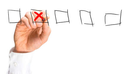 Man placing a red cross in a set of hand-drawn check boxes on a virtual interface over a white background with copyspace, close up view of his hand. photo
