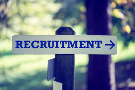 Recruitment signboard on a wooden post with a right pointing arrow. photo