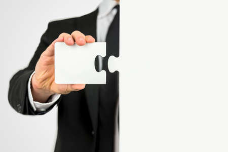 Businessman with a piece of the puzzle standing ready to fit the two matching shapes together Stock Photo