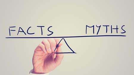 Männlich Hand zeichnen eine Wippe mit Worten Fakten und Mythen im perfekten Gleichgewicht, getönten Retro-oder Instagram-Effekt. Standard-Bild
