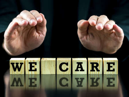 Man holding his hands protectively over words We care on a row of wooden cubes photo