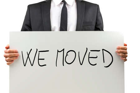 moved: Businessman holding white board with We moved sign on it. Stock Photo