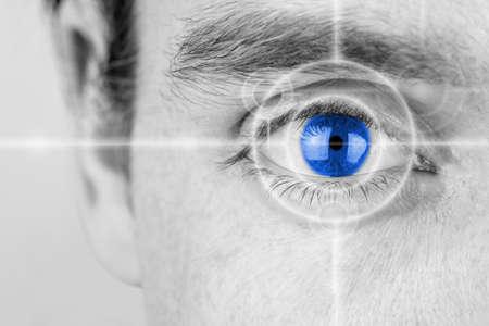 ビジョン コンセプトのグレースケール画像を選択的に青い彩られてきた彼のアイリスに焦点を当てた十字と目をマンします。