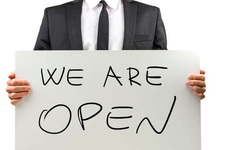 reachable: Businessman holding white board with We are open sign. Stock Photo
