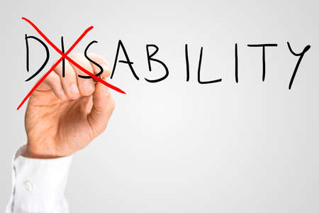 ability: Overcoming a disability concept with a man writing the word Disability on a virtual interface and then crossing through the - Dis - with a red marker pen as a motivational call to overcome adversity.