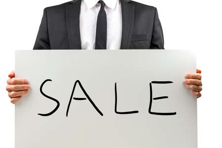 discounting: Businessman promoting a Sale holding up a white placard or sign with the handwritten word - Sale - in front of his body, closeup torso view.