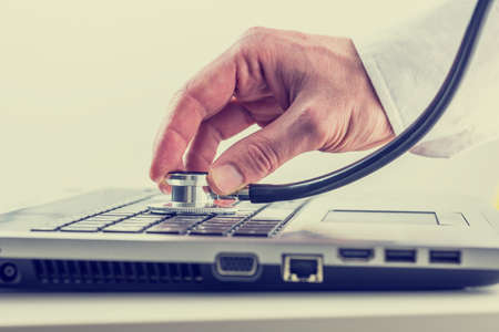 Man checking his laptop computer with a stethoscope holding the disk over the keyboard as he looks for viruses and malware, toned retro or instagram effect.