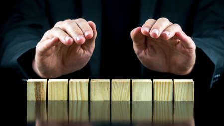 block note: Conceptual image with protective hands over eight wooden cubes or blocks. Ready for your text. Stock Photo