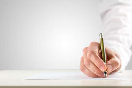 机の上に空白の紙の上の書き込みを開始するために、ボールペンを保持している白のスリーブと男性の手のクローズ アップ