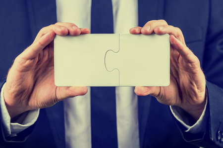 interlocked: Businessman holding two blank white interlocked puzzle pieces with copyspace for your text conceptual of teamwork, problem solving or meeting a business challenge, close up view with a vintage effect. Stock Photo