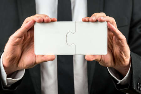 interlocked: Businessman holding two interlocked blank white jigsaw puzzle pieces in his hand depicting the completion of a deal, solution to a problem or overcoming a challenge.