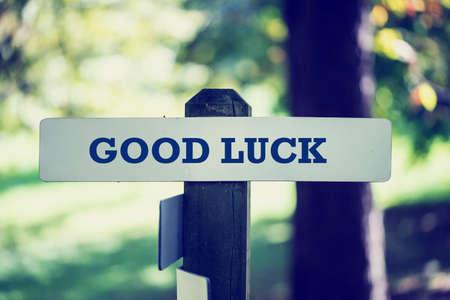 buena suerte: Señal rústica vieja con la frase ¡Buena suerte, al aire libre en el bosque soleado