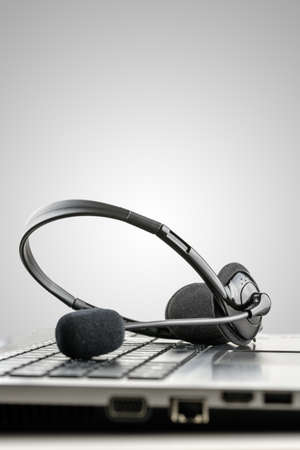 Headset on laptop computer conceptual of telemarketing, customer service or online help. Isolated over grey background. photo