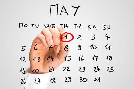 kalender: Männliche Hand Markierung auf einem Monatskalender, auf einem virtuellen Bildschirm platziert, die am 1. Mai, Tag der Arbeit, Tag der Arbeit oder Maifeiertag. Lizenzfreie Bilder
