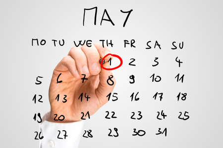 first day: Male hand marking on a monthly calendar, placed on a virtual screen, the date of May 1,  International Workers Day, Labour Day or May Day.
