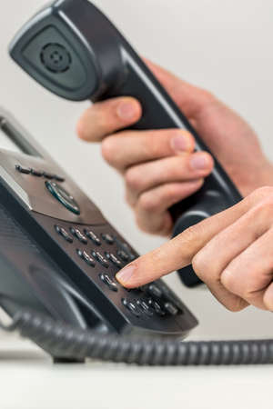 landline phone: Close up view of the hands of a man dialing out on a landline telephone instrument using his finger to punch in the numbers on the keypad in a communications concept. Stock Photo