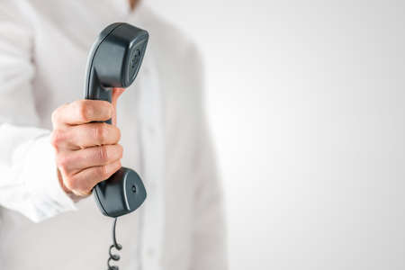 phone receiver: Man holding a landline telephone receiver or handset in his hand with a dangling cord, close up view of the instrument against his white shirt.