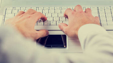 shirtsleeves: View from the mans perspective of his hands typing on a computer keyboard inputting information and data, toned retro
