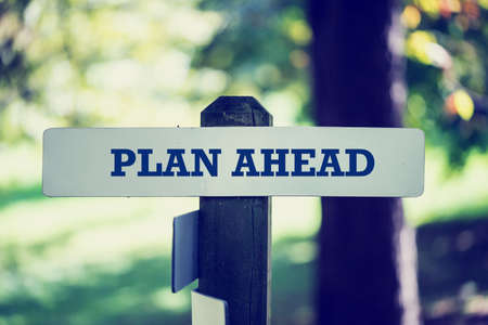 guideline: Old rustic signpost with the phrase Plan ahead, outdoors in sunny woodland with a faded vintage or retro effect to the image.