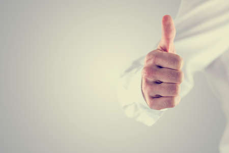 image of a man giving a thumbs up gesture of approval and success on a grey background with copyspace. photo