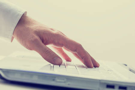Closeup of male hand using white laptop computer. Conceptual of online business or e-learning  photo