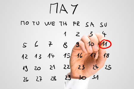 circling: Man circling the date of 11th May with a red marker pen on a hand-drawn calendar for the month of May on a virtual interface to remind him that it is Mothers Day to commemorate mothers and motherhood