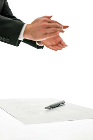 Businessman clapping his hands applauding a colleague, at an event or speech or for a successful business venture with a pen and paperwork below, isolated on white. photo