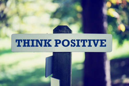 conclusive: Retro instagram style image of a motivational message Think positive written on wooden signpost in wooodland.