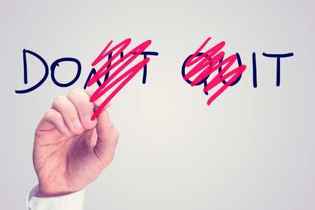Dont Quit - Do It, conceptueel beeld met een man schrobben door letters in de woorden Dont Quit het omzetten van hen om het te doen met een rode pen in een motiverende boodschap van hoop en doorzettingsvermogen. Stockfoto