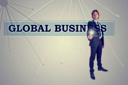 activating: Global Business concept with a stylish young businessman standing at a virtual interface activating a navigation bar with the words - Global Business - on a grey background with antennae. Stock Photo