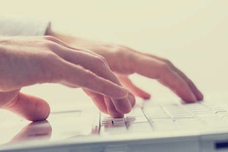 operating key: Close up faded effect retro style image of the hands of a man typing on a laptop keyboard. Stock Photo