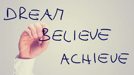envision: Male hand writing Dream Believe Achieve on virtual screen Stock Photo
