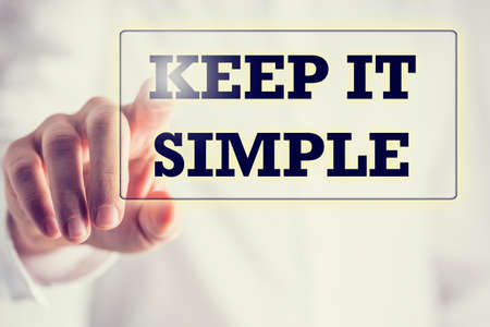 easy: Keep It Simple in a navigation bar on a virtual screen with a businessman touching it to activate it from behind conceptual of simplicity, clarity and easy understanding in business and in life.