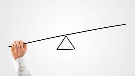 injustice: Man constructing a seesaw with a rod and triangle on a virtual interface to weigh up the balance between various concepts and see which carries the most importance
