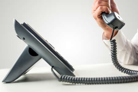 Side view of a black business landline telephone with the receiver held by a male hand with white shirt sleeve. Stock Photo