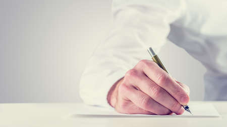 copy writing: Vintage retro style image of a man signing a document or writing notes on a sheet of paper, close up of his hand with copyspace to the left.