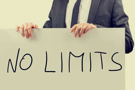 Conceptual retro style image of the hands of a businessman in a suit holding up a handwritten rectangular white sign saying - No Limits.