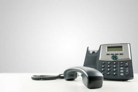 Close-up of a black business landline telephone with the receiver off-hook, on an empty desk, with copy space on the grey background. Conceptual of customer service or customer support.