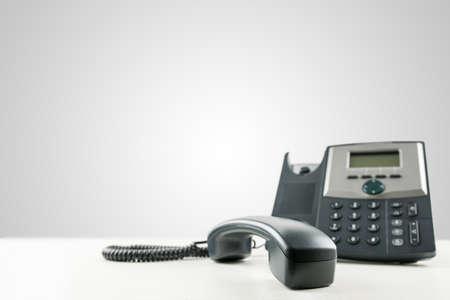 Close-up van een zwarte zakelijke vaste telefoon met de ontvanger van de haak, op een leeg bureau, met kopie ruimte op de grijze achtergrond. Conceptuele van de klantenservice of klantenondersteuning.