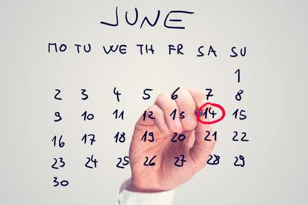 14th: Mano masculina que marca 14 de junio - D�a Mundial del Donante de Sangre - en el calendario virtual. Foto de archivo